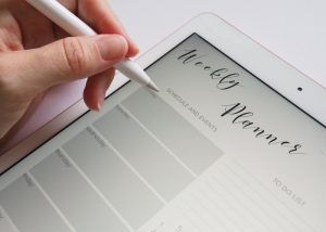 a woman creating a schedule in her weekly planner