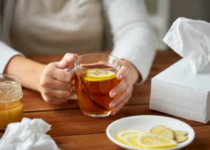 woman with the flu sat at a table holding a glass of lemon and ginger tea with tissues scattered around