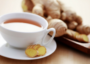 close up of a glass of ginger tea with fresh ginger in the background