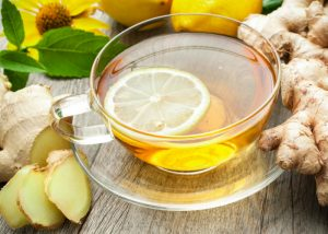 lemon and ginger tea in a clear glass cup and saucer
