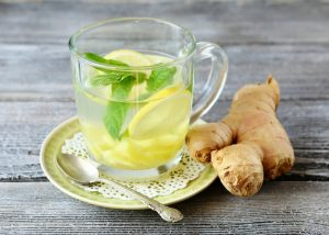 glass of lemon and ginger tea with a sprig of mint leaf