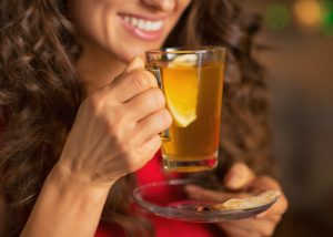 woman smiling and holding a glass of lemon and ginger tea