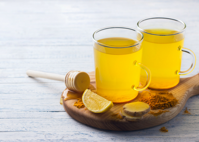 two glasses of turmeric ginger honey tea on a wooden board