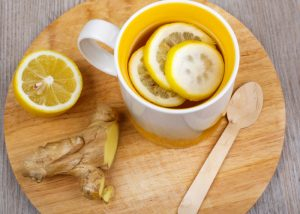 top down view of a mug of lemon and ginger tea on a wooden board with half a lemon and fresh ginger on the side