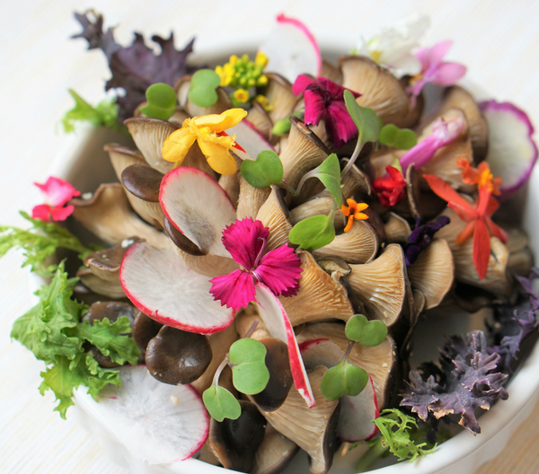 a fresh paleo-friendly raw salad with mushrooms and edible flowers