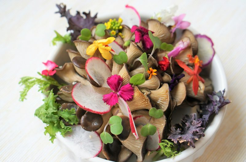 Fresh paleo-friendly raw salad with mushrooms and edible flowers
