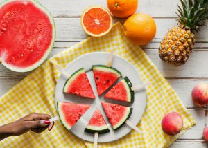 watermelon on sticks, half a watermelon and other fruits on a table