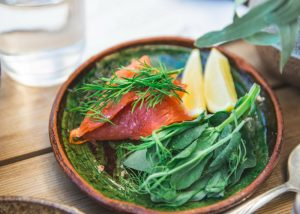 fresh greens and salmon with lemon wedges in a wooden bowl
