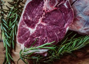a well marbled raw steak with sprigs of rosemary on a cutting board