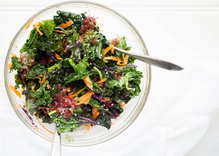 a healthy kale salad in a glass bowl on a white background