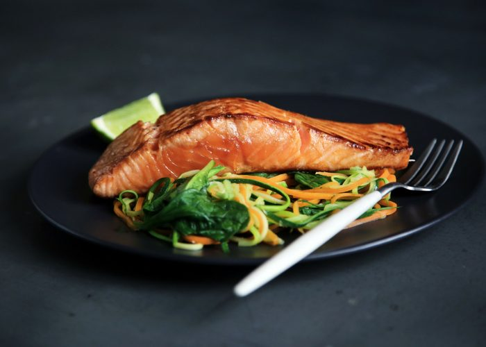 roasted salmon fillet on a bed of spiralized veggies on a black plate