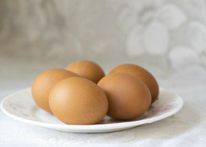 5 brown eggs on a white plate