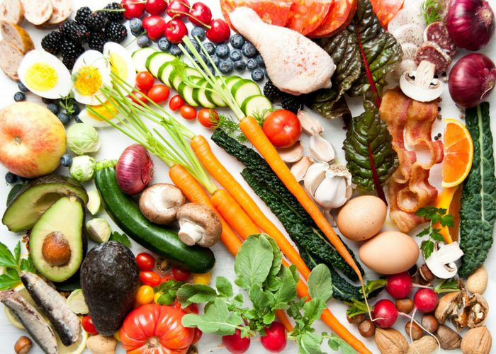 paleo diet foods including fresh vegetables, fruits, nuts, eggs, and meat on a table