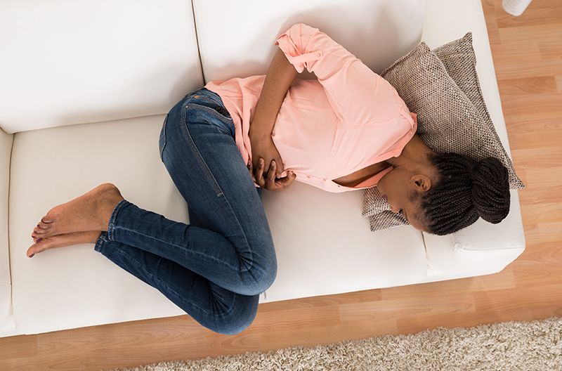 Woman clutching stomach due to period pain and cramps