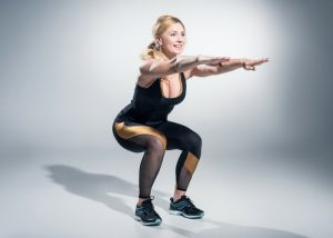 a woman doing hiit bodyweight squats on a gray background
