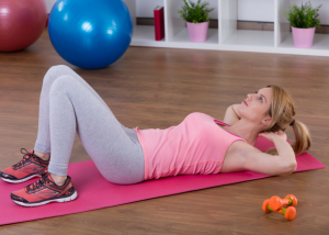 woman doing ab crunches on a pink yoga mat in her living room