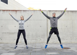 woman and man doing jumping jacks outdoors