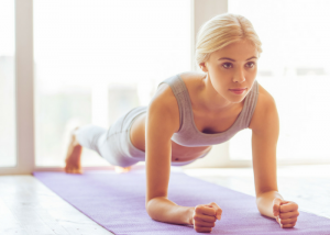 woman doing planks on a purple yoga mat