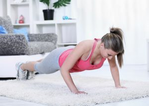 woman doing push ups in her living room on a plush white carpet