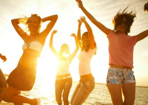 a group of girls dancing on the beach at sunset