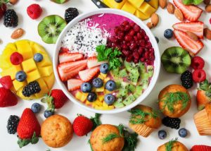 a healthy fruit bowl with strawberries, mangoes, kiwis, blueberries, pomegranate seeds, and lots of other fruits around it on a table