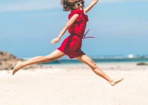 a woman in a red jumpsuit and sunglasses jumping on the beach