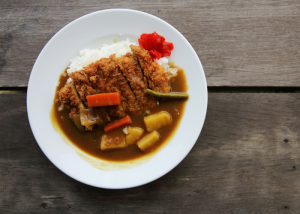a plate of japanese curry with white rice and fried pork cutlet