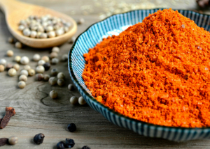 a pile of red curry spice on a blue dish