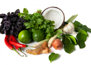 fresh ingredients for a curry such as chilis, cilantro, coconut, ginger, garlic, onions