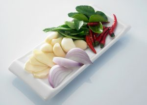fresh ingredients for a curry on a white plate
