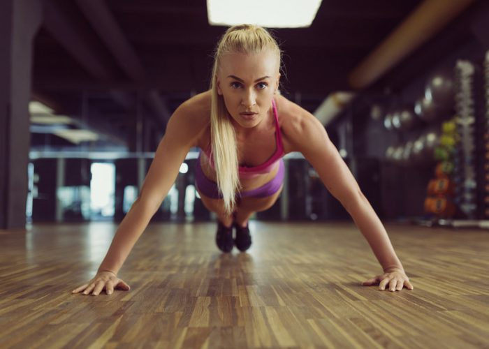 blonde woman doing planks in a gym on a wood floor