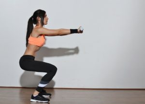 woman in black workout leggings doing squats
