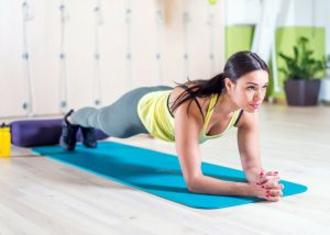 woman in plank position on blue yoga mat