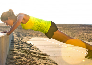 woman doing elevated push ups outdoors by the beach