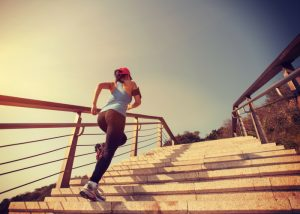 woman in black workout leggings running up stairs outdoors