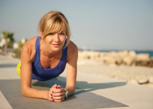 woman doing HIIT plank exercise by the beach