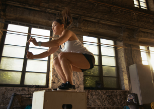 woman doing HIIT box jumps on a crate in a gym