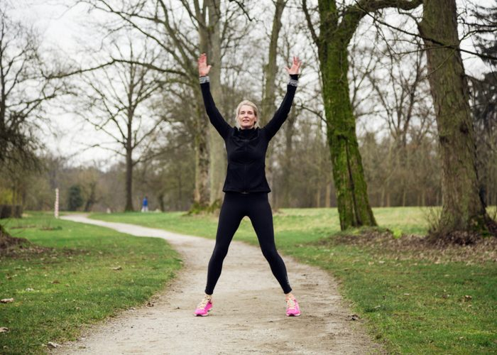 woman in a black workout suit doing jumping jacks outdoors in a park