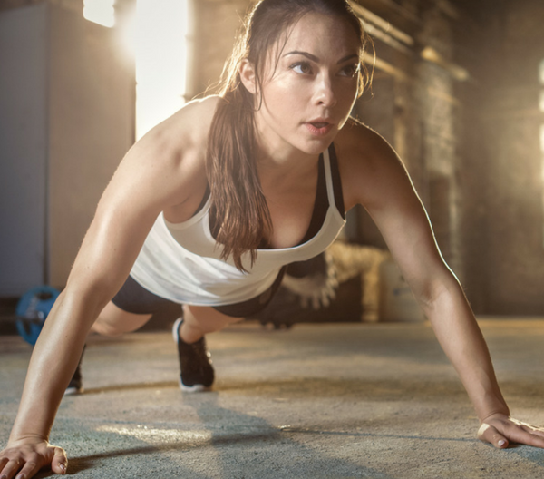 woman doing pushups on the floor in a gym
