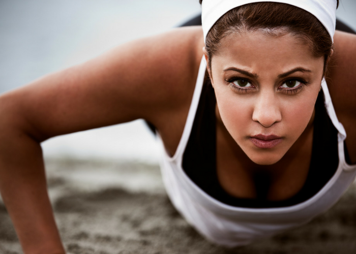 close up of a woman in workout clothes doing push ups on the sand