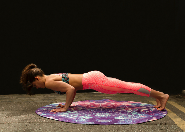 woman in yoga outfit doing push ups on a round purple mat