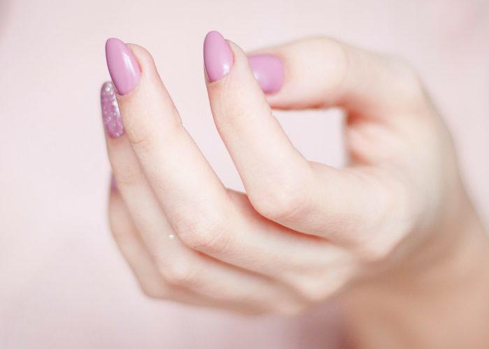 a woman's hand with nicely manicured pink nails