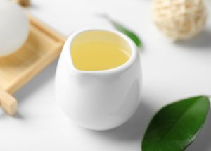 tea tree oil in a small white cup