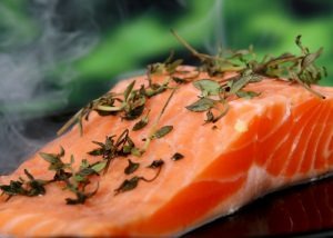 close up of a salmon fillet sprinkled with thyme leaves cooking on a pan