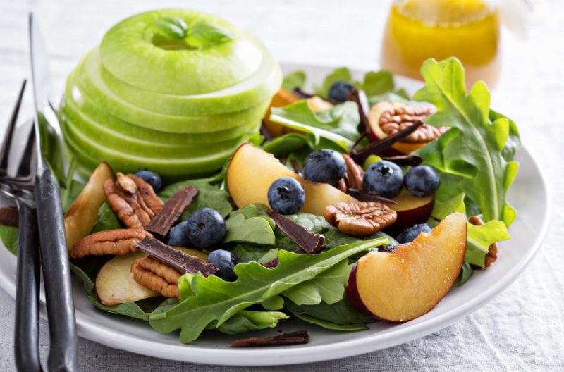 Plate of alkaline diet foods such as apple, blueberries, dark leafy greens, and nuts