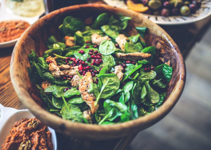 a wooden bowl with spinach salad, grilled chicken slices, and pomegranate seeds