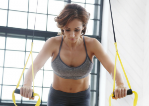 woman doing suspension exercises in front of a window