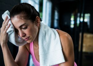 Woman wiping her sweat with a towel at the gym