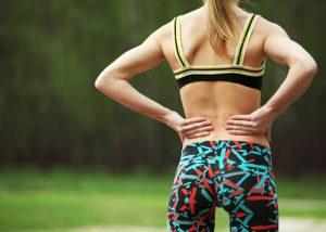 The back of a woman in fitness gear with her hands on her waist