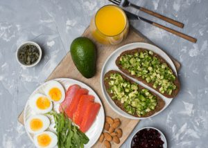 A healthy breakfast with avocados, orange juice, hard boiled eggs, salmon, nuts